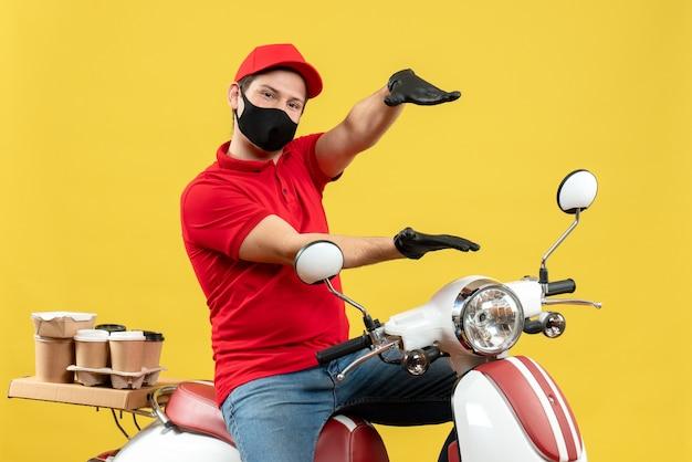 Vista superior del adulto joven con blusa roja y guantes de sombrero en máscara médica entregando orden sentado en scooter sintiéndose seguro sobre fondo amarillo