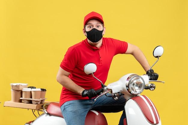 Vista superior del adulto joven con blusa roja y guantes de sombrero en máscara médica entregando orden sentado en scooter sobre fondo amarillo
