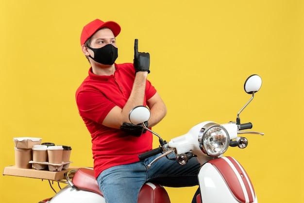 Vista superior del adulto joven confiado con blusa roja y guantes de sombrero en máscara médica entregando orden sentado en scooter mostrando uno sobre fondo amarillo