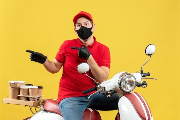 Vista superior del adulto joven confundido con blusa roja y guantes de sombrero en máscara médica entregando orden sentado en scooter apuntando algo sobre fondo amarillo