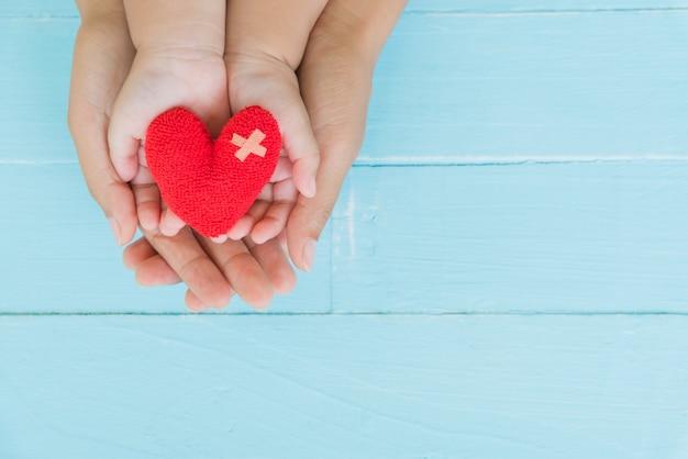 Vista superior de adulto y niño con corazón rojo en las manos, relaciones familiares felices