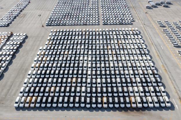 Vista superior aérea de autos nuevos alineados en el puerto para importación y exportación