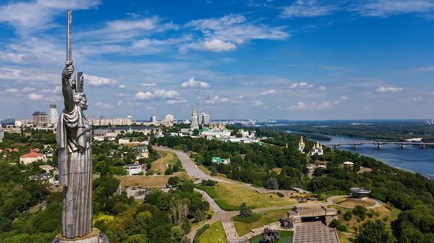 Vista superior aérea del monumento estatua de la patria de kiev en las colinas desde arriba y el paisaje urbano, la ciudad de kiev, ucrania