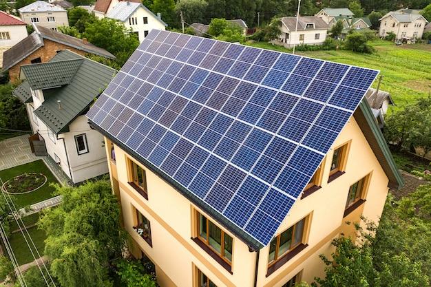 Vista superior aérea de la nueva casa residencial moderna casa de campo con azul brillante sistema de paneles fotovoltaicos fotovoltaicos en el techo. concepto de producción de energía verde ecológica renovable.