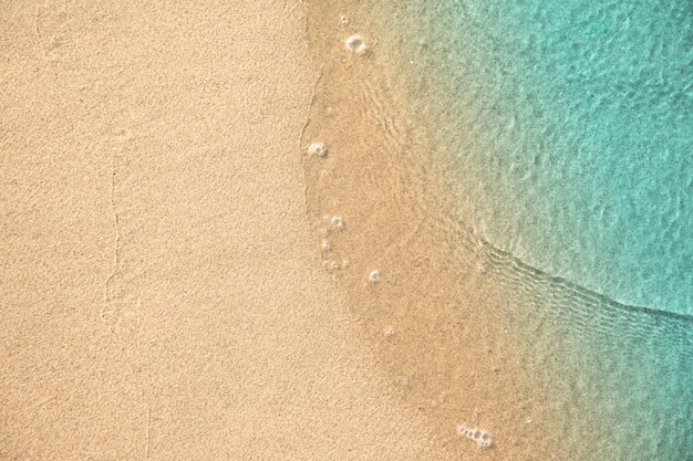 Vista superior de agua tocando arena en la playa