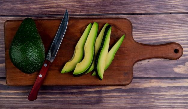 Vista superior de aguacates enteros y en rodajas con un cuchillo en la tabla de cortar sobre fondo de madera