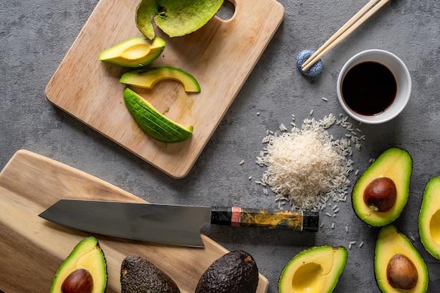 Vista superior de aguacates frescos, una tabla de cortar y un cuchillo, arroz y palillos sobre una superficie gris