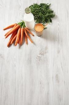 Vista superior aislada en la mesa de madera, cosecha de zanahoria de la granja que se encuentra cerca de la botella y el vaso lleno de una mezcla de jugo fresco natural y leche con una pajita dorada en ella