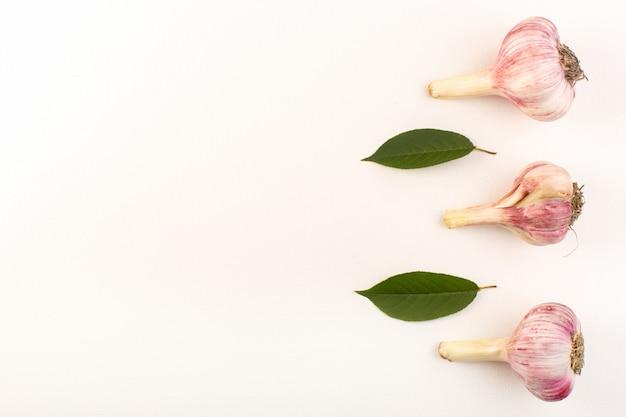 Una vista superior ajos enteros maduros frescos aislados forrados en el fondo blanco ingrediente de comida de alimentos vegetales