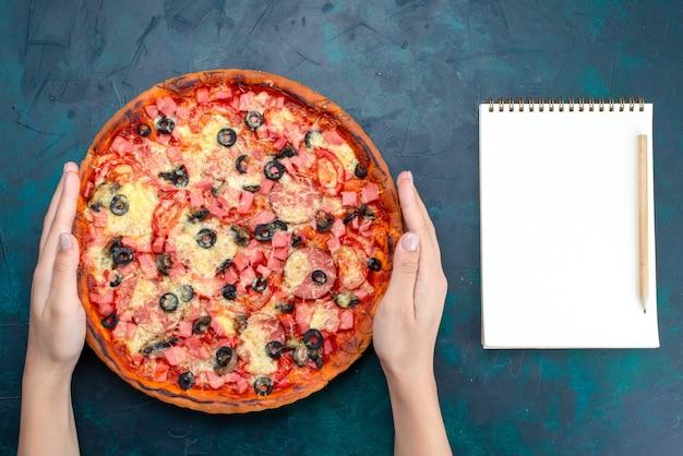 Vista superior al horno deliciosa pizza con aceitunas, salchichas y queso con bloc de notas sobre fondo azul.