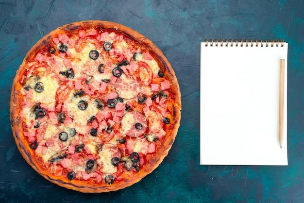 Vista superior al horno deliciosa pizza con aceitunas, salchichas y queso sobre fondo azul claro.