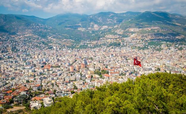 Vista superior de alanya en la montaña con la bandera de turquía y el fondo de la ciudad - hermoso hito de viaje de paisaje de alanya turquía