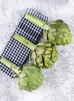 Vista superior de alcachofas en un paño de picnic y gris claro