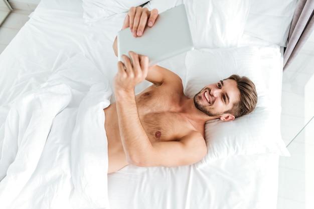 Vista superior del alegre joven relajado acostado y usando tableta en la cama
