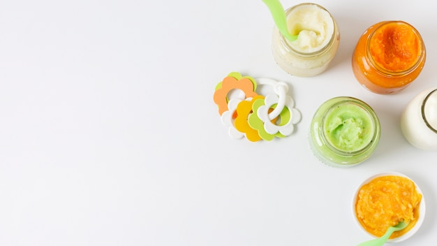 Vista superior de alimentos para bebés sobre fondo blanco.