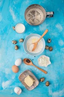 Vista superior de alimentos como harina, mantequilla, queso cottage con leche, huevo, pimienta negra sobre fondo azul.