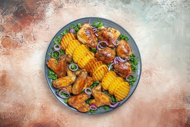 Vista superior de alitas de pollo alitas de pollo patatas fritas hierbas de cebolla en la mesa