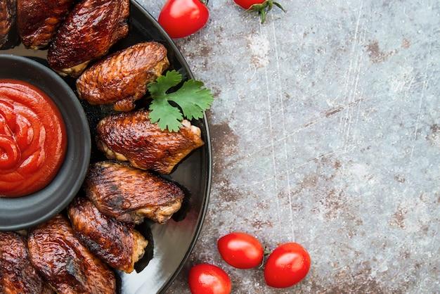 Vista superior de alitas de pollo asadas en placa con salsa de tomate sobre fondo grunge