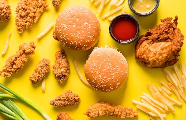 Vista superior de alitas de pollo frito, hamburguesas y papas fritas con salsas