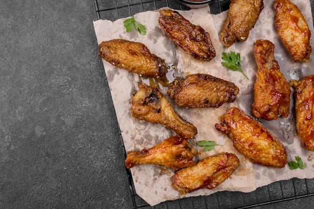 Vista superior de alitas de pollo frito y piernas en rejilla de enfriamiento con espacio de copia