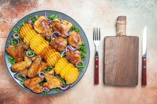 Vista superior de alitas de pollo patatas hierbas de pollo cebollas cuchillo tenedor la tabla de cortar
