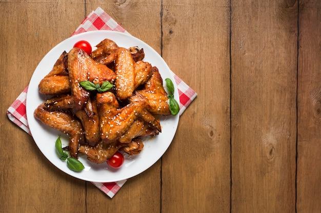 Vista superior de alitas de pollo en un plato con semillas de sésamo y espacio de copia