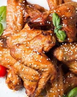 Vista superior de alitas de pollo en un plato con semillas de sésamo