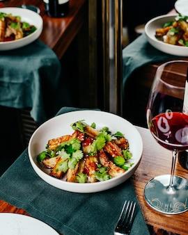 Una vista superior de alitas de pollo en rodajas con ensalada de verduras y vino tinto en la mesa, comida, cena, restaurante