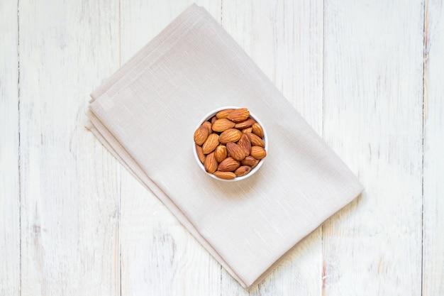 Vista superior de almendras tostadas en tazón de porcelana blanca sobre servilleta textil y mesa de madera blanca