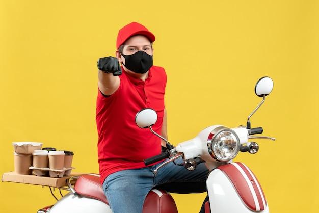 Vista superior del ambicioso adulto joven con blusa roja y guantes de sombrero en máscara médica entregando orden sentado en scooter sobre fondo amarillo