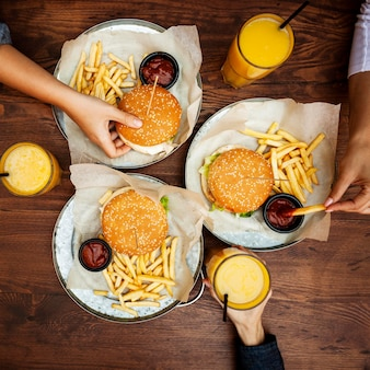 Vista superior de amigos comiendo hamburguesas con papas fritas