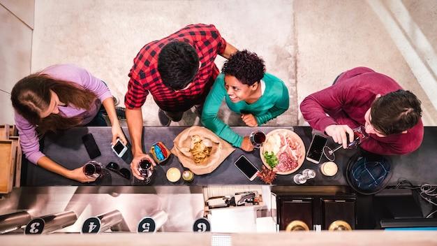 Vista superior de amigos multirraciales que se divierten hablando y bebiendo vino tinto en el restaurante bar de moda
