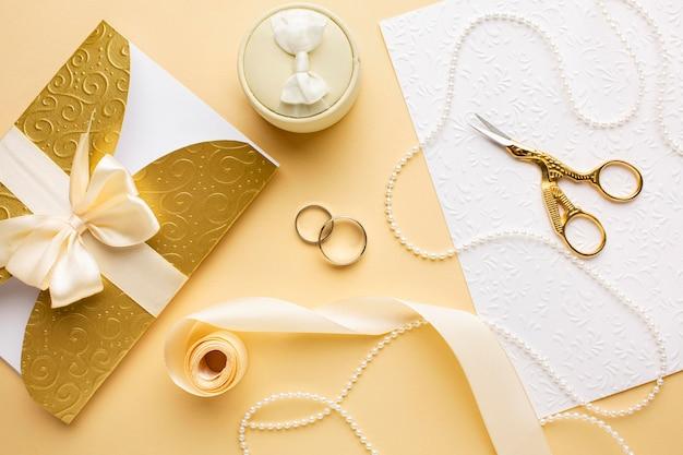 Vista superior de anillos de boda y cinta con tijeras
