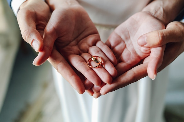 Vista superior de anillos de boda en manos de los recién casados.