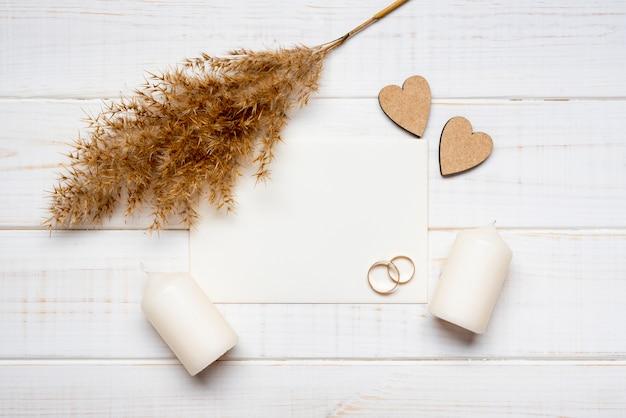 Vista superior anillos de boda con velas en la mesa