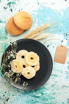 Vista superior de los anillos de piña seca dentro de la placa en la superficie azul pastel hornear fruta galleta dulce azúcar cookie