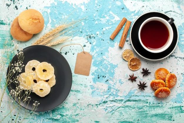 Vista superior de los anillos de piña seca con pequeñas galletas y una taza de té sobre fondo azul pastel hornear galletas de frutas dulces galletas de azúcar