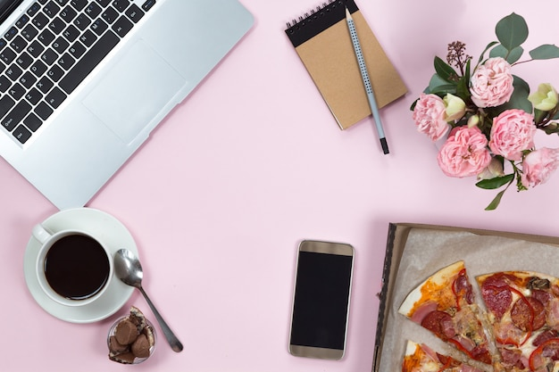 Vista superior de aparatos de oficina, café, teléfono móvil y pizza.