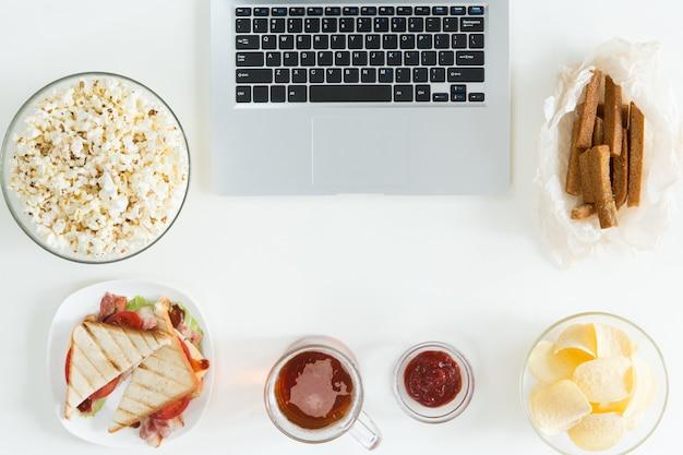 Vista superior de aperitivos y alimentos poco saludables con la computadora portátil en el escritorio blanco, concepto de jugador