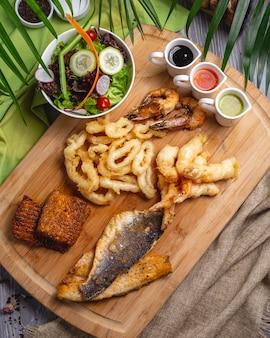 Vista superior aperitivos de mariscos pescado camarón calamar con salsas y ensalada de verduras