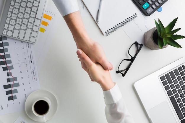 Vista superior del apretón de manos sobre la mesa de trabajo