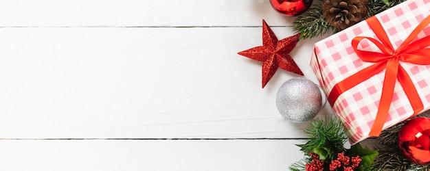 Vista superior del árbol de navidad y caja de regalo de vacaciones de navidad y año nuevo con adornos decorativos sobre fondo de mesa de madera blanca. concepto de fondo de banner de regalos y felicitaciones con espacio de copia.