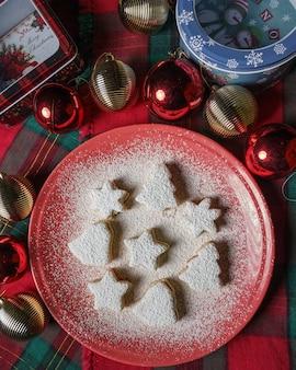 Vista superior del árbol de navidad, campana y galletas estrella cubiertas con azúcar en polvo