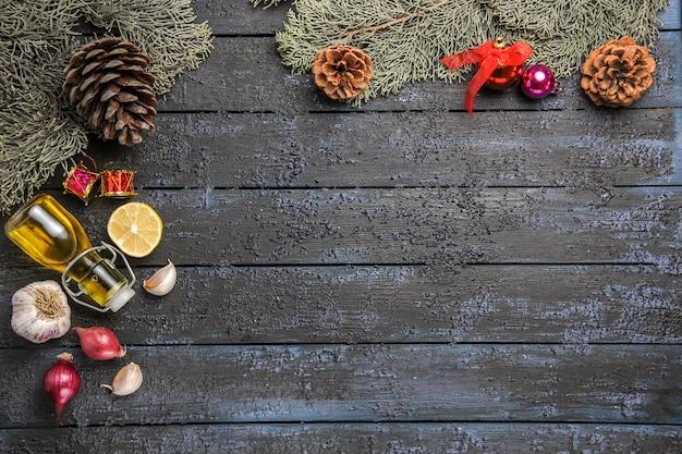 Vista superior del árbol de navidad con juguetes y ajo en el escritorio oscuro, juguete de color, vacaciones de limón.