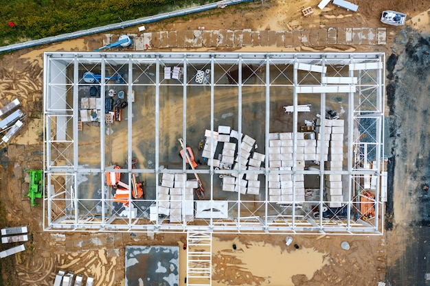 Vista superior del área de trabajo y gran estructura de acero de un gran edificio comercial. construyendo un almacén
