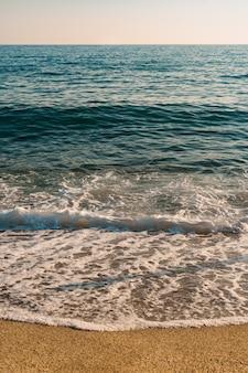 Vista superior de la arena al encuentro del agua de mar
