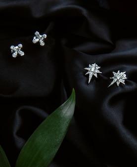 Vista superior de aretes de plata esterlina con diamantes con tachuelas en la pared negra