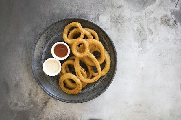 Vista superior de aros de cebolla con diferentes salsas en un plato sobre la mesa