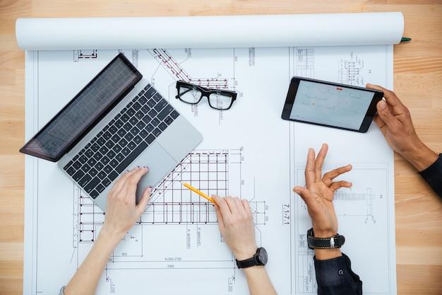 Vista superior de arquitectos de hombre y mujer que discuten planos y usan computadora portátil y tableta