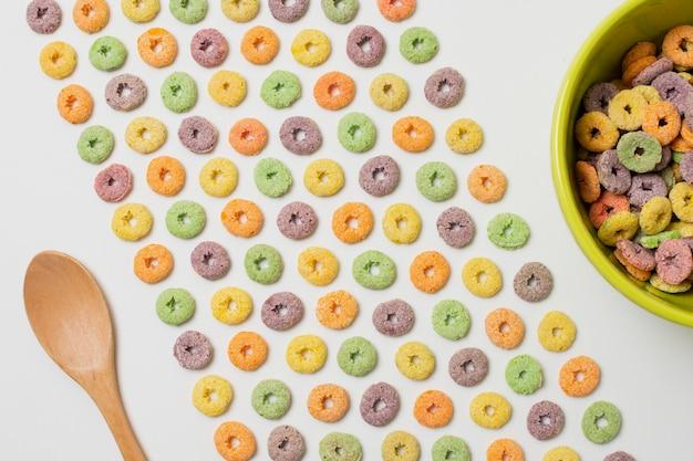 Vista superior arreglo con cereales coloridos sobre fondo blanco.
